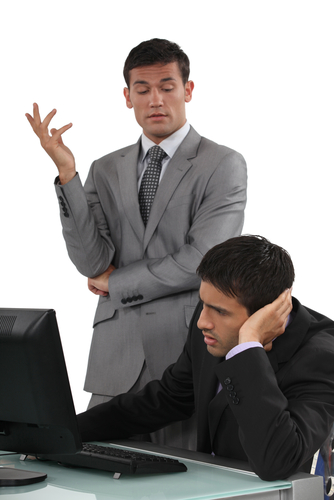 Manager standing over employee