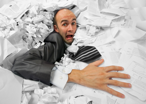 Man being swallowed up by too much paper